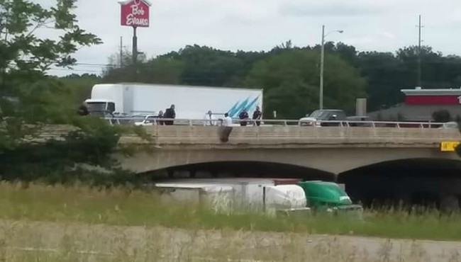 Man on Apple Avenue overpass over US-31 in Muskegon