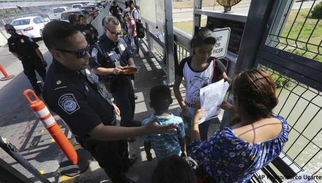 Border agent checking papers of asylum seeker