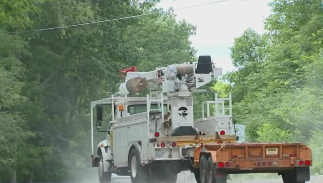 Dust rises from road as utility truck moves