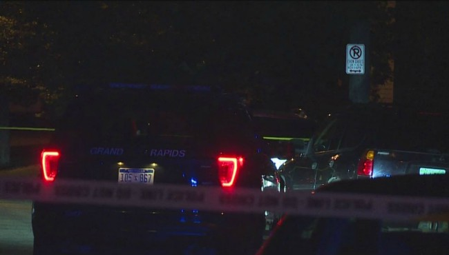 Crime tape surrounds parked police vehicles