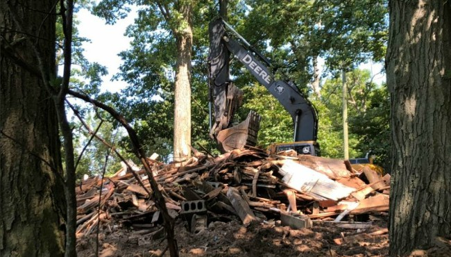 excavator perched over rubble of home