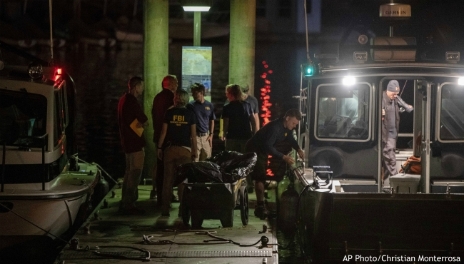 Authorities and FBI investigators cart away evidence taken from the scuba boat Conception in Santa Barbara Harbor at the end of their second day searching for the remaining divers still missing from the deadly pre-dawn fire on Tuesday, Sept. 3, 2019, in Santa Barbara, Calif. A fire raged through the boat Conception carrying recreational scuba divers anchored near an island off the Southern California Coast Monday, leaving multiple people dead. (AP Photo/Christian Monterrosa)