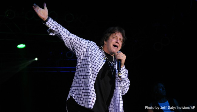 Eddie Money singing into microphone