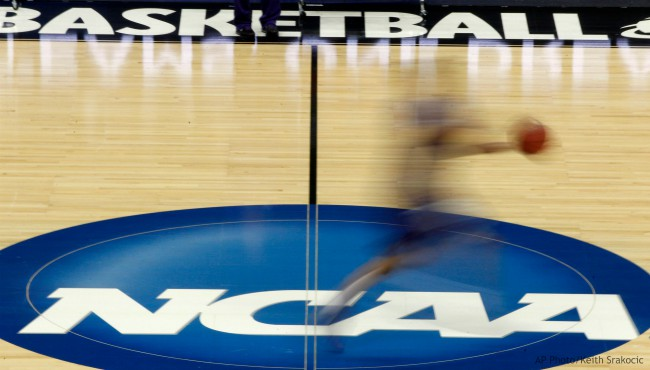 In this March 14, 2012, file photo, a player runs across the NCAA logo during practice at the NCAA tournament college basketball in Pittsburgh. (AP Photo/Keith Srakocic, File)