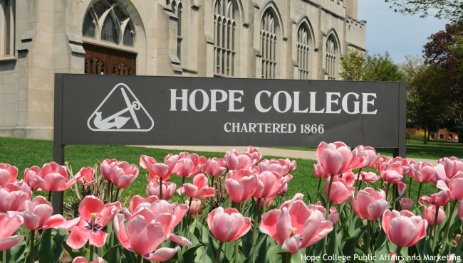 Hope College sign in front of Dimnent with pink tulips in front. (Courtesy of Hope College Public Affairs and Marketing)