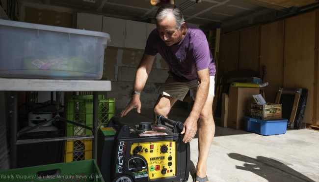 Joe Wilson pulls his generator out in the garage of his home, which is in an area that is expected to lose power early Wednesday, in the East Foothills area of San Jose, Calif., Tuesday, Oct. 8, 2019. (Randy Vazquez/San Jose Mercury News via AP)