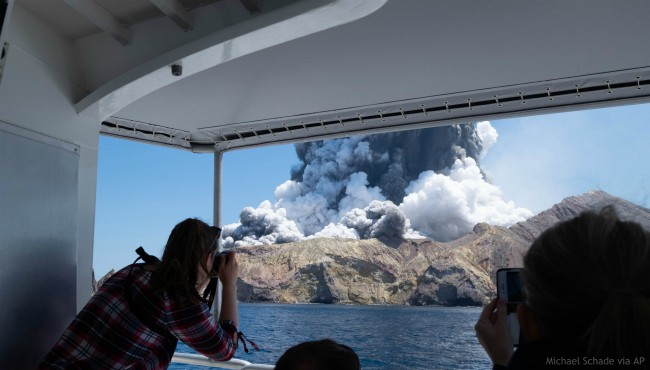 In this Dec. 9, 2019, photo provided by Michael Schade, tourists on a boat look at the eruption of the volcano on White Island, New Zealand. (Michael Schade via AP)