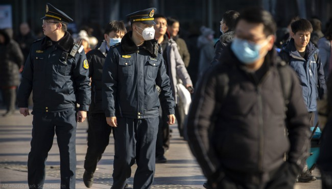 A security officer wears a face mask as he patrols outside of the Beijing Railway Station in Beijing, Monday, Jan. 20, 2020. (AP Photo/Mark Schiefelbein)