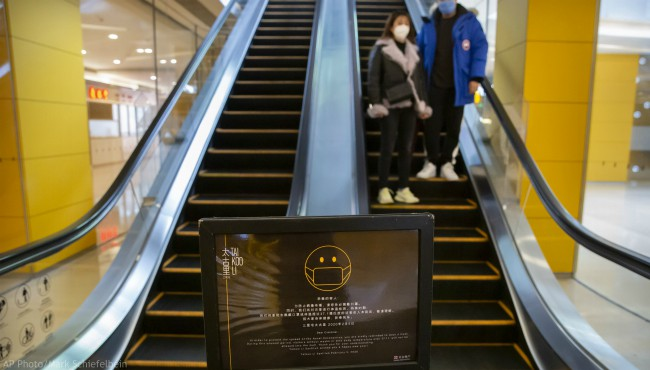 A sign reminds customers to wear face masks as a couple rides an escalator at a shopping center in Beijing, Friday, Feb. 14, 2020. (AP Photo/Mark Schiefelbein)