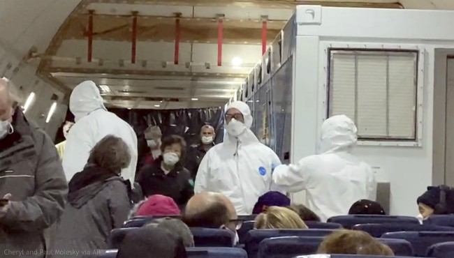 In this image from a video taken on Monday, Feb. 17, 2020, U.S. passengers who evacuated off the quarantined cruise ship the Diamond Princess and officials wait for the takeoff of a Kalitta Air airplane bound for the U.S., at Haneda airport in Tokyo. (Cheryl and Paul Molesky via AP)
