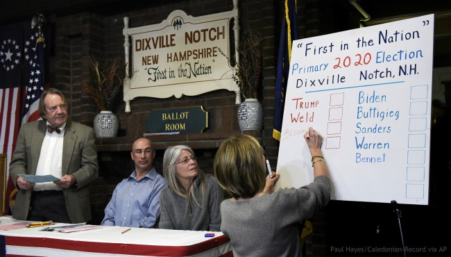 From left, moderator Tom Tillotson, supervisor of the checklist Joe Casey and town clerk Deborah Tillotson look on as Coralie Stepanian marks a Republican write-in vote on the board for Democratic candidate and former New York Mayor Michael Bloomberg during the presidential primary election midnight vote at The Balsams Resort in Dixville Notch, N.H., early Tuesday, Feb. 11, 2020. (Paul Hayes/Caledonian-Record via AP)