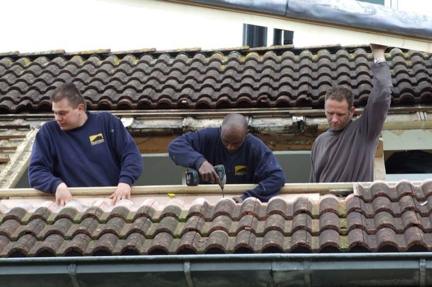 Drie mannen isoleren dak van een huis