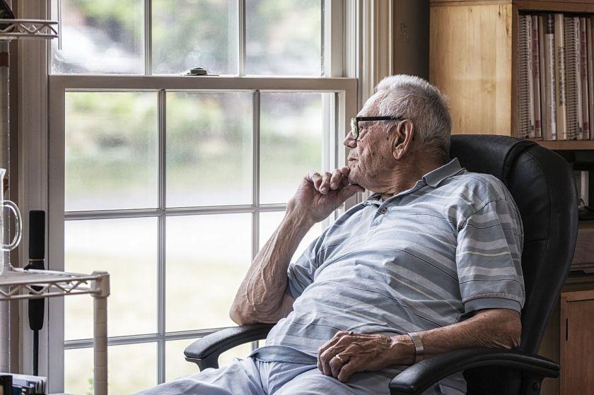 Oudere man kijkt uit raam van zijn woning