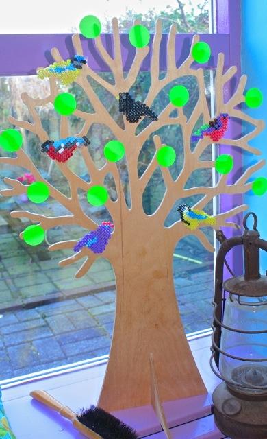 seizoensboom in de vensterbank met vogeltjes van strijkkralen