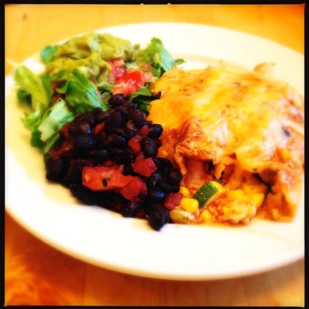 Enchiladas on a plate with guacamole salad and black beans