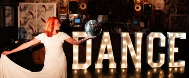 Our DANCE letter lights lighting up the bar with a bride dancing