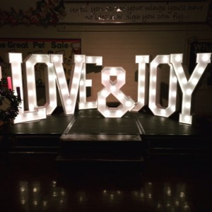 LOVE & JOY illuminated letters lighting up the stage for Christmas