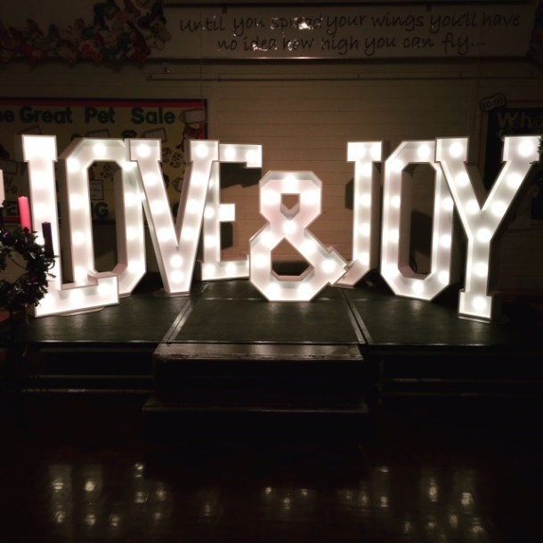 LOVE & JOY lighted words decorating the stage for a Christmas party celebration