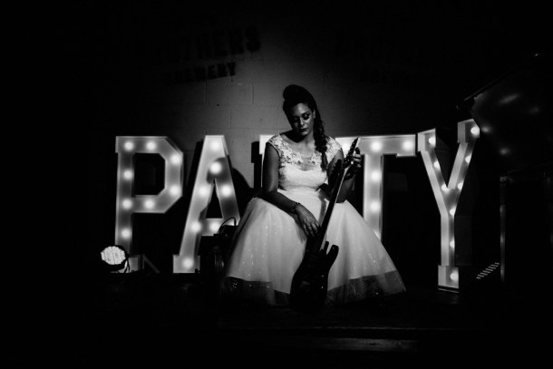 A bride and her guitar with PARTY letters in lights decorating a stage