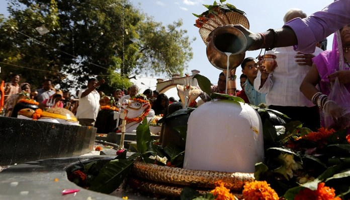 A Hindu devotee pours milk over a Shivling (a symbol of Lord Shiva) while carrying his child at a temple during the Mahashivratri festival in Ahmedabad, India, March 7, 2016. Hindus across the country celebrate Mahashivratri, better known as Lord Shiva's wedding anniversary. REUTERS/Amit Dave