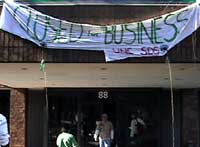 Students hang banner in front<br>of Rep. David Price's office,<br>Chapel Hill, Feb. 16.