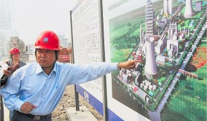 China in 2010 became the world's largest investor in clean energy. It is the largest producerof solar panels and of wind energy. Here, an engineer points to a diagram of the GreenGencoal-fired, low-emission power plant that went online this year.