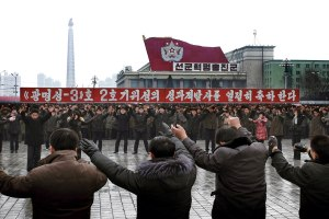 Koreans in Pyongyang, Dec. 14, dance near banner reading 'We celebrate the launch of the satellite.'
