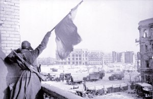 Soviet soldier waving the red flag over the central plaza of Stalingrad in 1943.