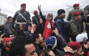 Spouse Basma Khalfaoui gives victory sign at Chokri Belaïd's funeral.