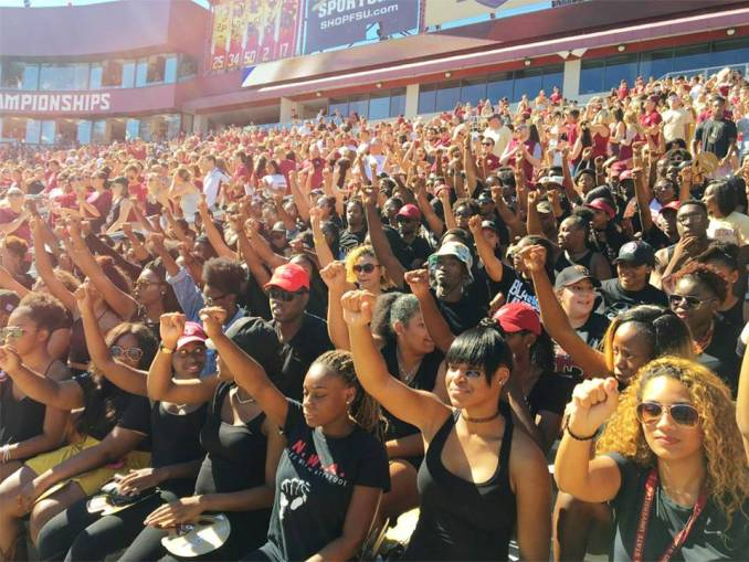 Florida State University students sit during national anthem, Oct. 8.