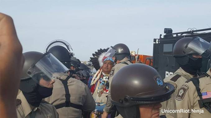 A Native elder in ceremonial dress, who was praying, is arrested by police and military at Oceti Sakowin Treaty Camp, Oct. 27.
