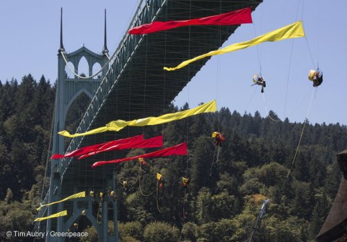 Protesters hang off St. Johns Bridge in Portland, Ore., trying to stop Shell Arctic oil driller from leaving port.