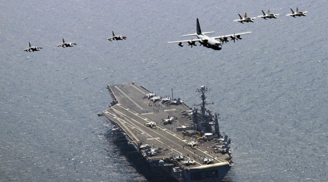 U.S. Marine Corps aircraft and jets over the aircraft carrier USS George Washington in the East Sea of Korea.