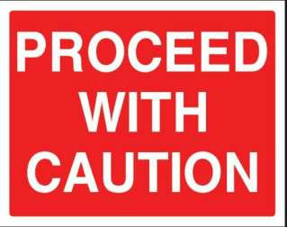 A red road sign that says proceed with caution