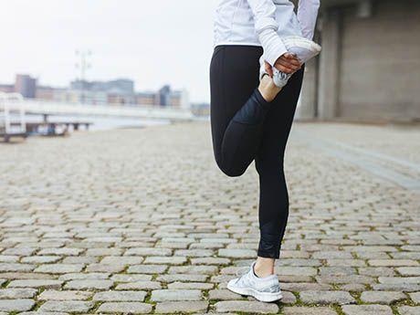 woman stretching her legs and holding running shoe