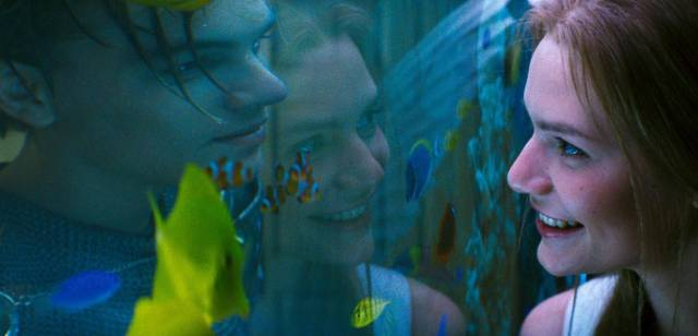 Juliet smiling at Romeo through a fish tank