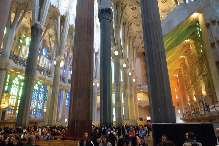 Inside the Sagrada Familia, with high, off-white columns. Yellow light streams in from the right, and blue from the left.