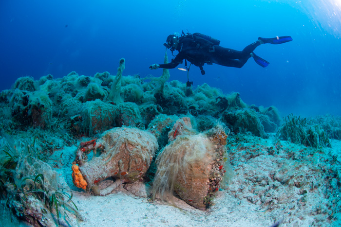 Diver surveys amphorae underwater