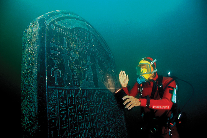 Underwater archaeologist inspects huge Egyptian stele with torch
