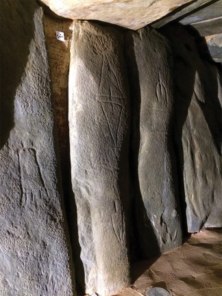 Long stones in the corridor. One is engraved with triangular images of schematic daggers.