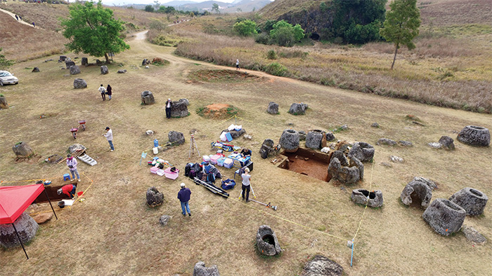 Aerial photo showing archaeologists excavating among the massive stone jars