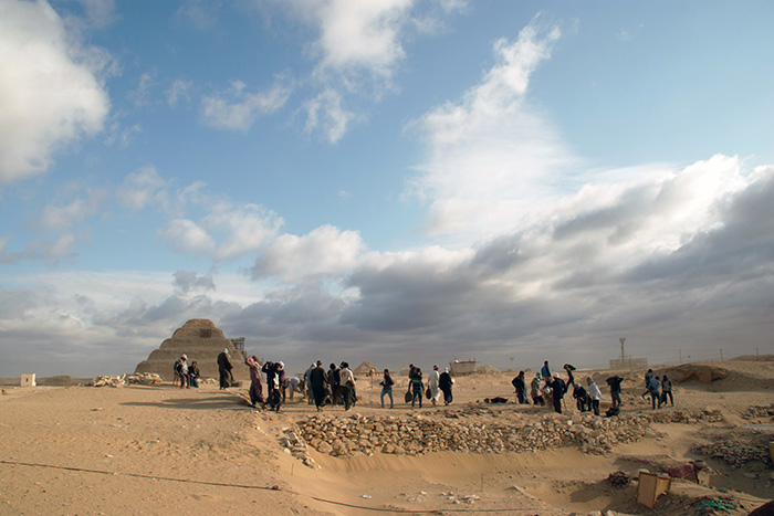 The excavation of Saqqara taking place, with a pyramid in the background