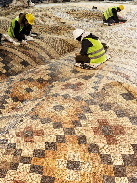 Conservators working on the rippled mosaic