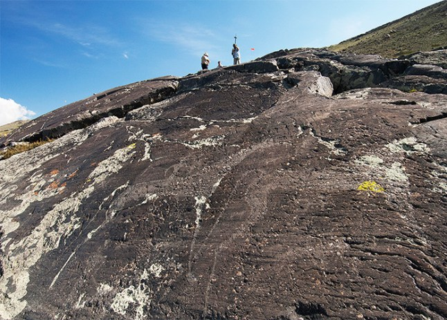 A steep rock face with a horse-shaped petroglyph. Researchers recording the petroglyph can be seen standing on top of the rock
