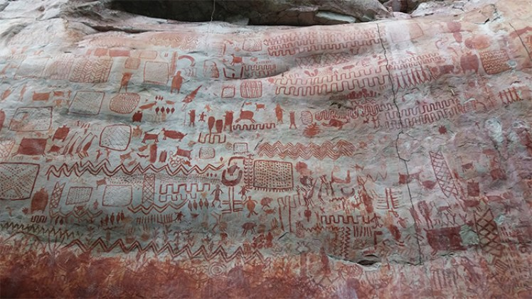 A large rock-face decorated with many red images showing human and animal figures and geometric patterns