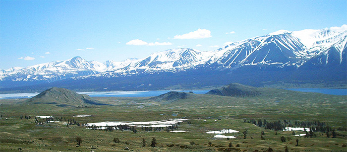 A range of snow-covered mountains, with a green landscape and lake in the foreground