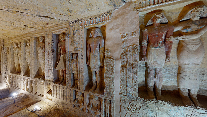 A section of the walls in the tomb decorated with statues of varying sizes and hieroglyphic inscriptions.