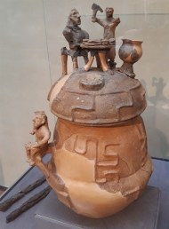 A clay urn with decoration on the lid representing a funeral banquet