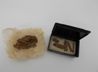 The box, open, with fragments of wood inside, and a pile of smaller fragments next to it.