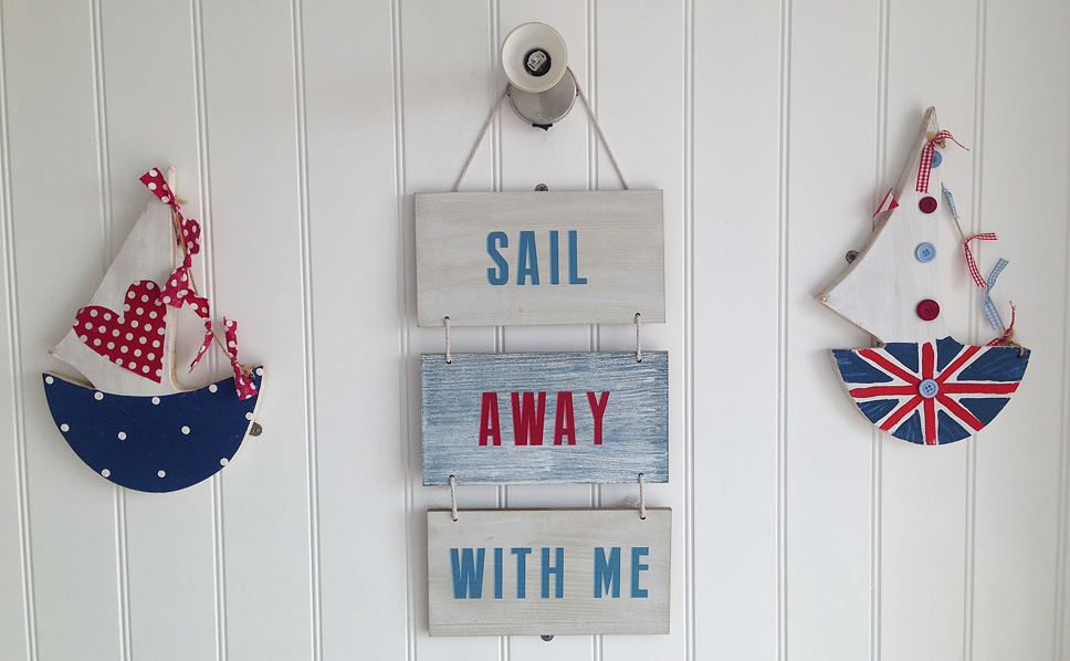 Hanging wooden slats with Sail, Away, With Me painted on them
